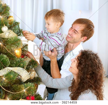 Happy Family Decorating Christmas Tree together. Father, Mother And Son. Cute Child.Kid
