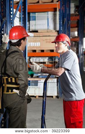 Mid adult foreman communicating with young coworker at warehouse