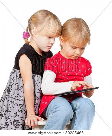 Two serious girls playing with a touch pad