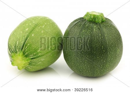 one light green and a green round zucchini cut zucchini (Cucurbita pepo) on a white background