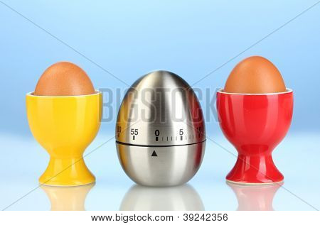 egg timer and egg in color stand on blue background