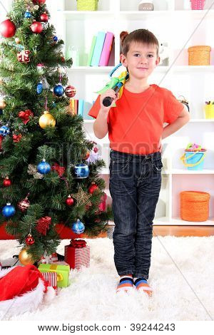 Little boy stands near Christmas tree with badminton rackets