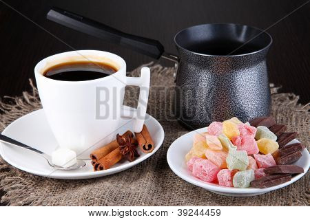 White cup of Turkish coffee with rahat delight and coffee maker on wooden table