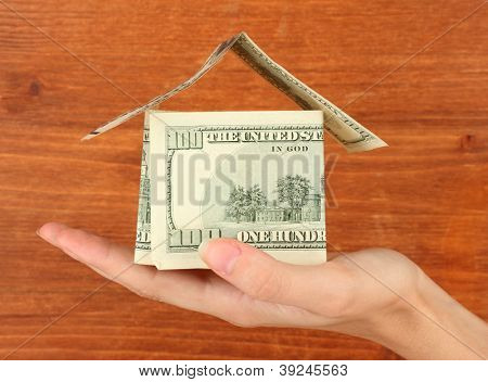 Hand holding a house made of dollars on wooden background close-up