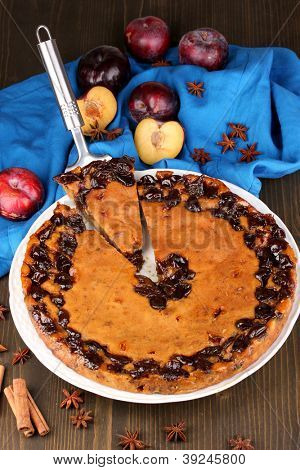 Tasty pie on plate with plums on wooden table
