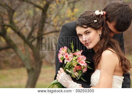 wedding, young groom kiss bride in love over autumn nature background, park fall outdoor