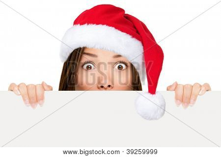 Santa hat woman showing christmas sign peeking over edge wearing red santa hat with funny expression. Mixed race asian chinese / caucasian woman portrait isolated on white background.