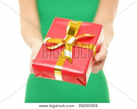 Gift. Woman giving red christmas gift / present. Closeup of woman holding and showing red Christmas present with gold ribbon on pure white background.