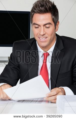 Happy young businessman reading document at desk in office