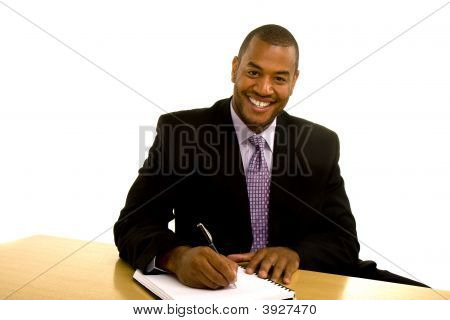 Black Man Writing At Desk And Smiling