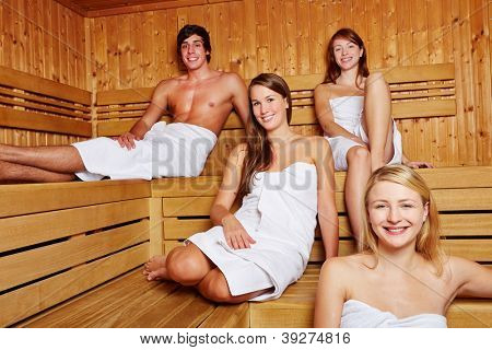 Smiling people sitting together in a mixed sauna