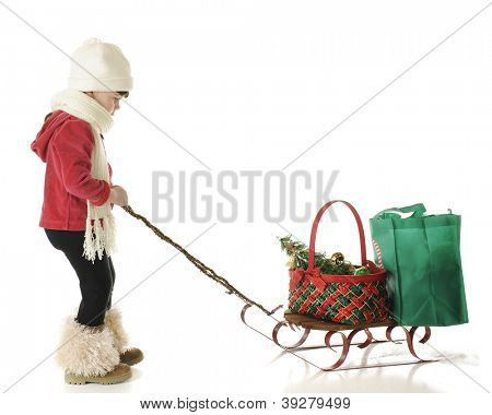 An adorable preschool girl dressed for winter, intently pulling a sled with a Christmas basket and green shopping bag.  On a white background with plenty of space for your text.