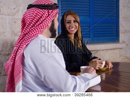 arabian couple relaxing in the garden drinking tea