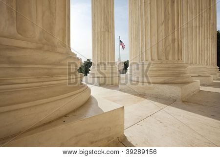 American Flag Viewed Between Columns Of Supreme Court Building