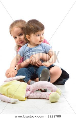 Siblings Brother And Sister Sitting On Floor With Doll