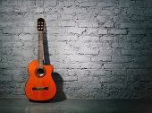 picture of string instrument  - Acoustic guitar leaning on grungy gray brick wall - JPG