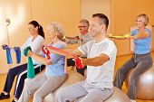 Reha sports for group of happy seniors in fitness center
