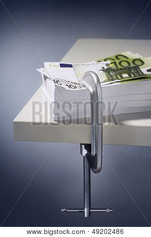 Pile of Euros clamped to table
