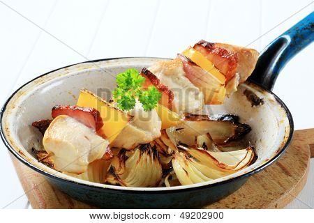 skewer with chicken meat, bacon and vegetable in a dirty pan