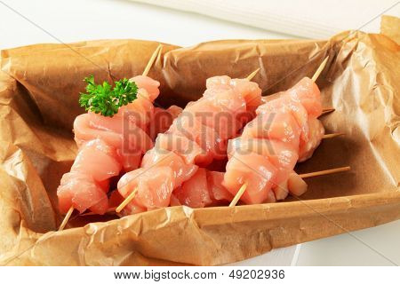 raw chicken skewers on a baking paper