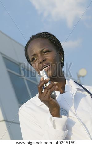 Female doctor speaking into dictaphone