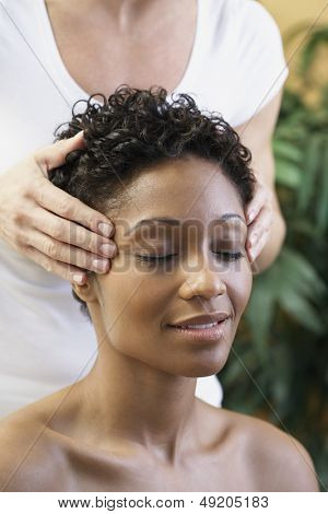 Young woman receiving facial massage