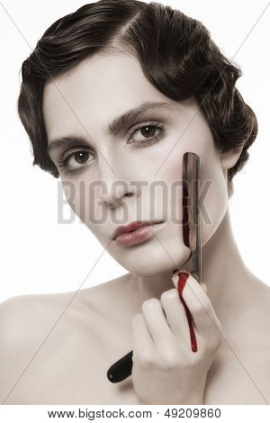 Close-up portrait of beautiful woman with bloody vintage razor in her hand