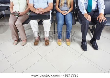 Feet of different people sitting in a waiting room