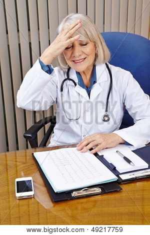 Elderly doctor in office has an idea and slaps his head