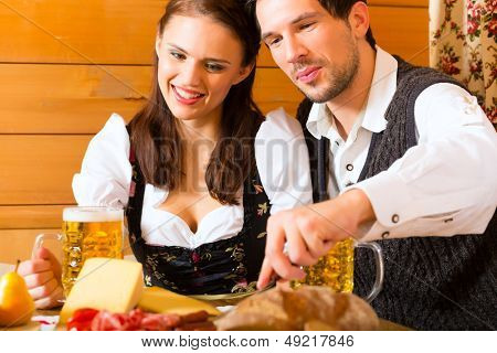 Couple in a traditional mountain hut having a meal with bread and cold cuts