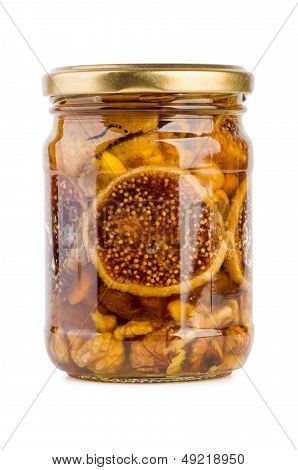 Glass jar filled with honey nuts and fruits