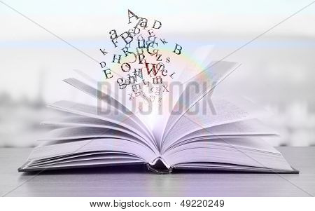 Open book with letters in shades of gray