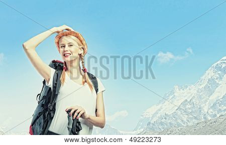 Pretty young woman tourist standing on top of mountain