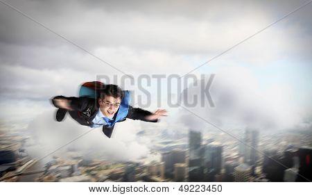 Imagem conceitual do jovem empresário voando com pára-quedas nas costas