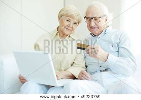 Senior couple with credit card and laptop during shopping through Internet