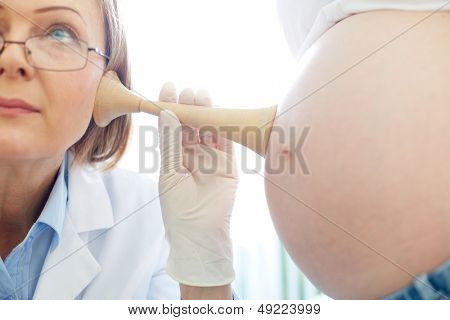 Mature gynecologist examining the belly of a pregnant young woman