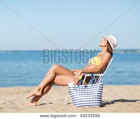 summer holidays and vacation - girl in bikini sunbathing on the beach chair