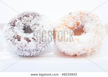 Chocolate And Vanilla Coconut Donuts On White Plate