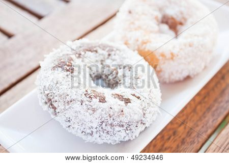 Chocolate And Vanilla Coconut Donuts On Wooden Table