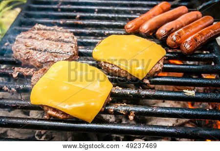 Hamburgers With Cheese And Hot Dogs On Grille