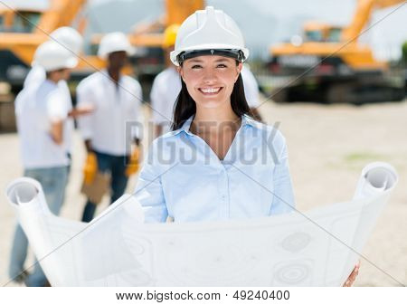 Female architect at a construction site holding blueprints