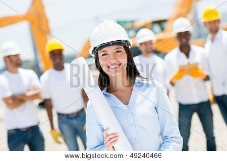 Female engineer at a construction site looking happy