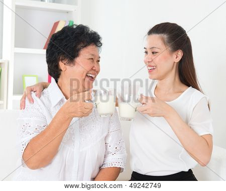 Drinking milk. Asian family drinking milk at home. Beautiful senior mother and adult daughter, healthcare concept.