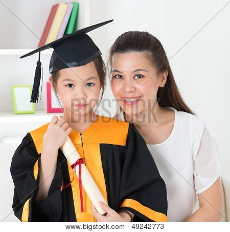 Asian school kid graduate in graduation gown and cap. Taking photo with mother.