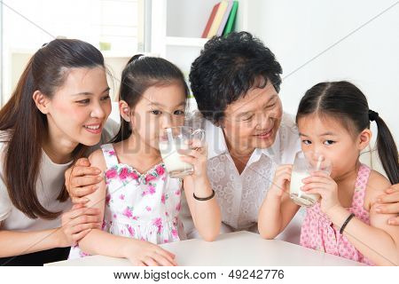 Drinking milk. Happy multi generations Asian family at home. Beautiful grandmother, mother  and granddaughters, healthcare concept.