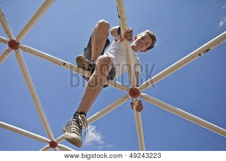 kid playing on monkey bars, view toward blue sky