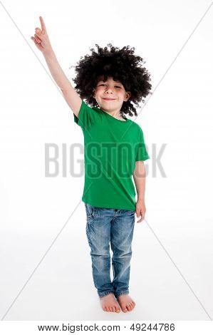 Boy Wearing A Big Black Wig Pointing His Finger In The Air.