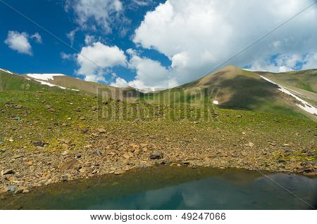 Small mountains with Colorful Lake and dark blue sky and clouds