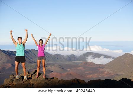 Happy cheering winning success outdoors couple excited having reached summit of mountain volcano , East Maui Volcano, Hawaii. Young multiracial sporty fitness couple in running outfit.