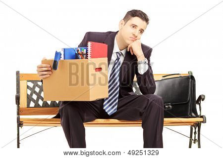 Disappointed redundant young man in a suit sitting on a bench with a box of belongings isolated on white background